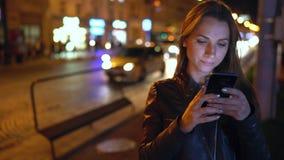 Attraktive Frau benutzt einen Smartphone beim Gehen durch die Straßen der Glättungsstadt stock video