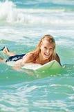 Attraktive Frau bodyboards auf Surfbrett Lizenzfreie Stockbilder