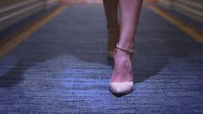 Attraktive Frau in den beige Schuhen gehend auf Teppichboden im langen Korridor stock footage
