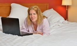 Attraktive Frau in den Pyjamas im Bett mit Laptop-Computer Lizenzfreie Stockfotografie