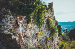 Attraktive Frau in der alten Festung Stari-Stange, Montenegro Brunettefrau im weißen Kleid geht um Schloss, die Magie Lizenzfreies Stockfoto