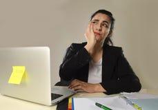 Attraktive Frau in der Anzugfunktion ermüdete und bohrte im Bürocomputertisch, der traurig schaut Lizenzfreies Stockbild