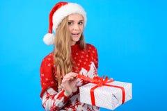 Attraktive Frau in der Weihnachts-Kleidung, die einen Präsentkarton öffnet lizenzfreie stockfotos