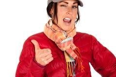 Attraktive Frau in der Winterabnutzung zeigend und blinzelnd Lizenzfreie Stockfotografie