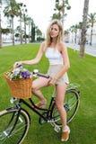 Attraktive Frau des blonden Haares, die für die Kamera mit Weinlesefahrrad aufwirft Stockbild