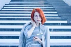 Attraktive Frau des Geschäfts mit einer Tablette in den Händen, die beiseite auf dem Hintergrund der Treppe im Geschäftszentrum s Lizenzfreie Stockfotos