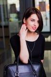 Attraktive Frau des Porträts mit einem Aktenkoffer in einem Mall Lizenzfreie Stockfotografie