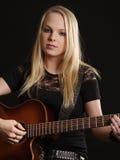 Attraktive Frau, die Akustikgitarre spielt Stockfoto