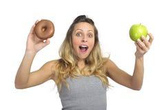 Attraktive Frau, die Apfel- und Schokoladendonut in der gesunden Frucht gegen süße Versuchung der ungesunden Fertigkost hält Stockbilder