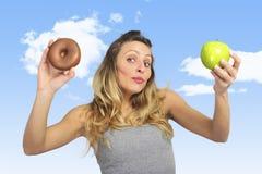 Attraktive Frau, die Apfel- und Schokoladendonut in der gesunden Frucht gegen süße Versuchung der ungesunden Fertigkost hält stockfotos