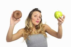 Attraktive Frau, die Apfel- und Schokoladendonut in der gesunden Frucht gegen süße Versuchung der ungesunden Fertigkost hält Lizenzfreies Stockfoto