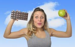 Attraktive Frau, die Apfel und Schokoriegel in der gesunden Frucht gegen süße Versuchung der ungesunden Fertigkost hält Lizenzfreie Stockbilder