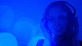 Attraktive Frau, die auf bunten Hintergrund der Musik hört Lizenzfreies Stockfoto
