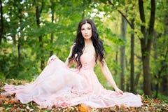 Attraktive Frau, die auf den Steinen im Park sitzt Herbst, Natur, Fall Lizenzfreie Stockfotos