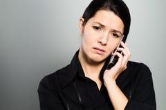 Attraktive Frau, die auf ein Gespräch hört Stockfotografie