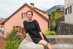 Attraktive Frau, die auf einem Hintergrund von europäischen Häusern aufwirft Lizenzfreie Stockfotografie