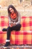 Attraktive Frau, die auf einer Bank mit einer Tablette sitzt Stockfotografie