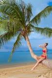 Attraktive Frau, die auf einer Palme ein Sonnenbad nimmt Stockfotografie