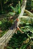 attraktive Frau, die auf hölzerner Hängebrücke sitzt lizenzfreie stockfotografie
