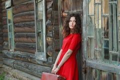 Attraktive Frau, die auf hölzerner Wand des alten Blockhauses mit Retro- Koffer sich lehnt Lizenzfreie Stockbilder