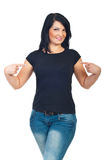 Attraktive Frau, die auf ihr T-Shirt zeigt Stockfotos