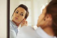Attraktive Frau, die auf ihre Ohrringe sich setzt Lizenzfreie Stockbilder