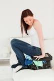 Attraktive Frau, die auf ihrem Koffer sitzt Stockbilder