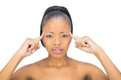 Attraktive Frau, die auf ihren Kopf zeigt und Kamera betrachtet Stockfotos