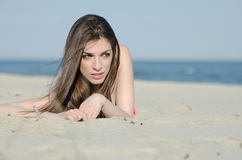 Attraktive Frau, die auf Sandabnutzungsbikini liegt Stockfotos