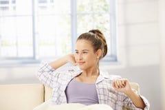 Attraktive Frau, die auf Sofa ausdehnt Lizenzfreie Stockfotografie