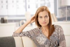 Attraktive Frau, die auf Sofa sitzt Stockfoto