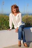 Attraktive Frau, die auf Wand sitzt Stockfotos