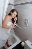 Attraktive Frau, die Aufruf im Badezimmer bildet Lizenzfreies Stockfoto