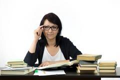 Attraktive Frau, die bei Tisch das Studieren sitzt Lizenzfreie Stockbilder