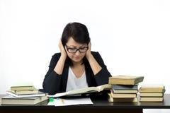 Attraktive Frau, die bei Tisch das Studieren sitzt Stockfoto