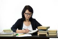 Attraktive Frau, die bei Tisch das Studieren sitzt Stockbild