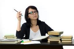Attraktive Frau, die bei Tisch das Studieren sitzt Lizenzfreies Stockfoto