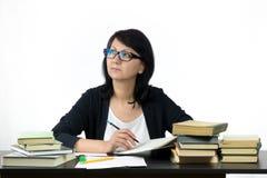Attraktive Frau, die bei Tisch das Studieren sitzt Stockfotos