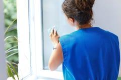 Attraktive Frau, die das Fenster wäscht Arbeitskraft Cleaning Company wor stockfotografie