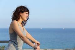 Attraktive Frau, die das Meer von einem Balkon aufpasst Stockfotos