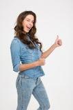Attraktive Frau, die Daumen blinzelt und sich zeigt Lizenzfreie Stockfotografie