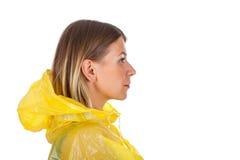 Attraktive Frau, die den gelben Regenmantel - lokalisiert trägt Stockbild