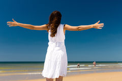 Attraktive Frau, die in der Sonne auf Strand steht Stockfotos