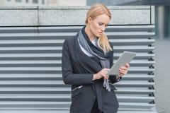 Attraktive Frau, die draußen eine Tablette verwendet Stockbild