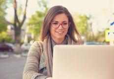 Attraktive Frau, die draußen Laptop verwendet lizenzfreie stockfotos