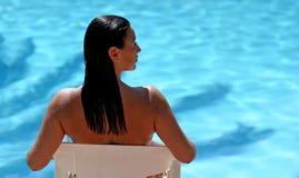 Attraktive Frau, die durch blauen sonnigen Swimmingpool sitzt Lizenzfreies Stockfoto