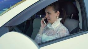 Attraktive Frau, die durch das Telefon im Auto spricht stock video