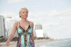 Attraktive Frau, die durch das Ufer geht Lizenzfreie Stockfotografie