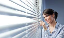 Attraktive Frau, die durch Vorhänge späht lizenzfreies stockbild