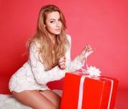 Attraktive Frau, die ein Geschenk öffnet Stockbild